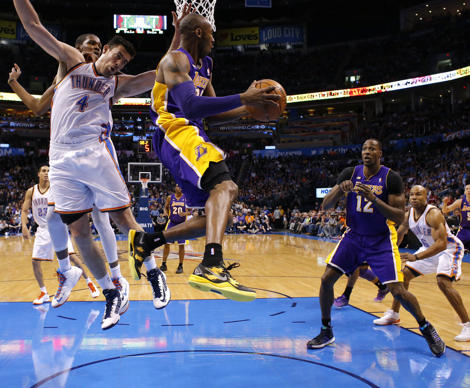 Los Angeles\' Kobe Bryant (24) looks to pass to Dwight Howard (12) as he passes by Oklahoma City\'s Nick Collison (4) during an NBA basketball game between the Oklahoma City Thunder and the Los Angeles Lakers at Chesapeake Energy Arena in Oklahoma City, Tuesday, March. 5, 2013. Photo by Bryan Terry, The Oklahoman