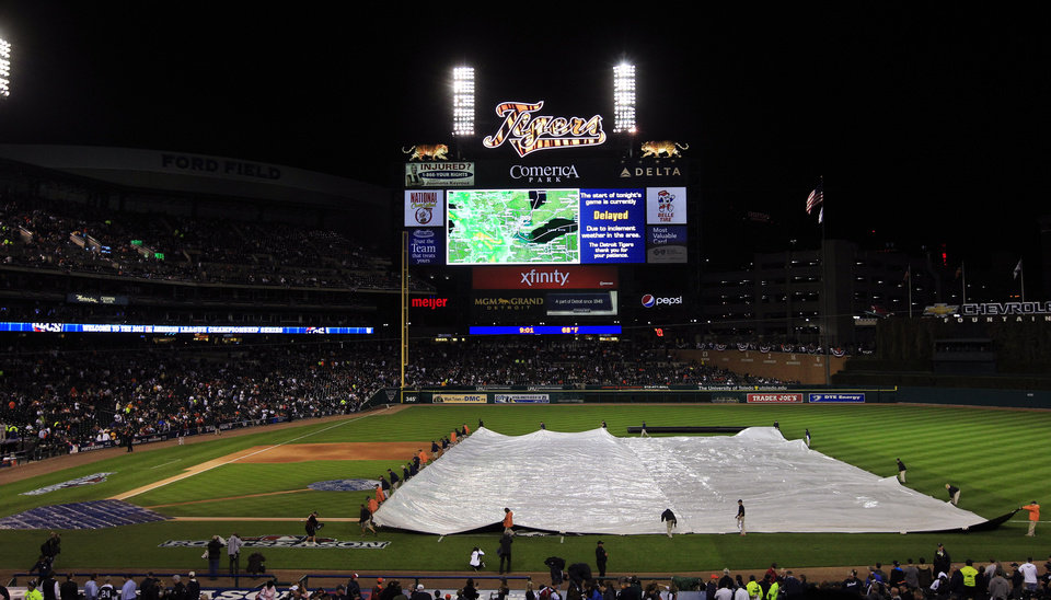 Photo -   Grounds crew members cover the field during a rain delay at Game 4 of the American League championship series between the Detroit Tigers and New York Yankees Wednesday, Oct. 17, 2012, in Detroit. (AP Photo/Carlos Osorio)