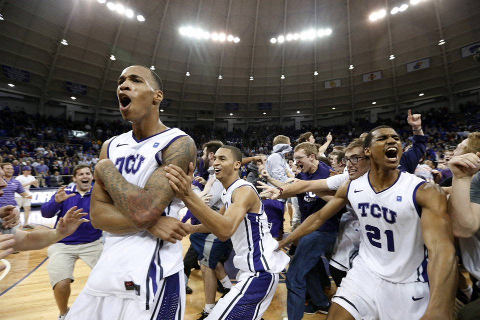 Photo - TCU forward Garlon Green, left, and guards Clyde Smith, and Nate Butler Lind (21) celebrate with the fans on the court after an NCAA college basketball game against Kansas on Wednesday, Feb. 6, 2013, in Fort Worth, Texas. TCU won 62-55. (AP Photo/Sharon Ellman)