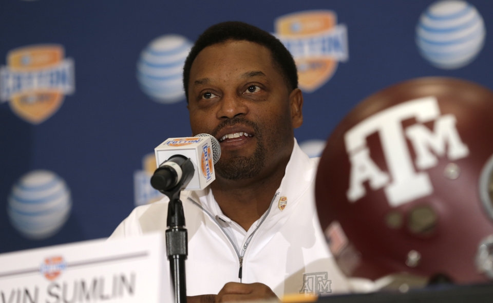 Photo - Texas A&M head coach Kevin Sumlin answers a question during a news conference leading up to the Cotton Bowl NCAA college football game Wednesday, Jan. 2, 2013, in Irving, Texas. Before Sumlin became a successful head coach, he was on Oklahoma head coach Bob Stoops  Stoops' staff. Before that, they were both assistant coaches recruiting the same area. Now Sumlin takes his Texas A&M team against Stoops' Sooners in a Jan. 4th Cotton Bowl matchup of former Big 12 rivals that are both 10-2 (AP Photo/LM Otero)