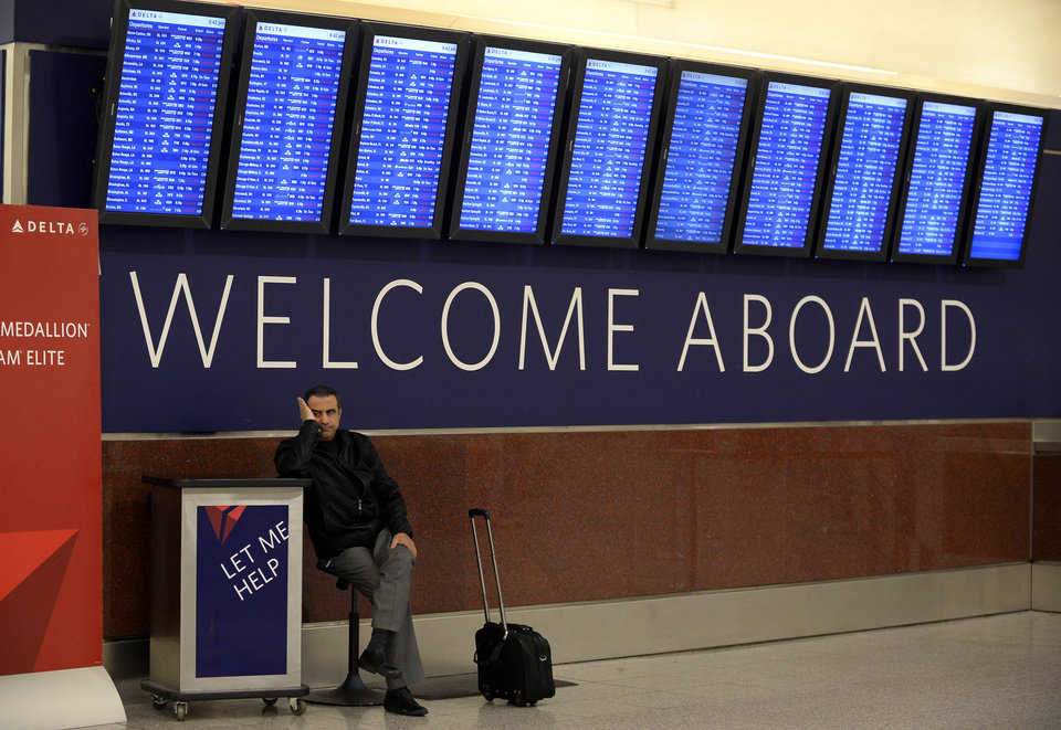 FILE - In this  Tuesday, Feb. 11, 2014, file photo, Airline passenger Hossam Shalaby, from Egypt, waits for his rescheduled flight to Orlando under the departure board showing hundreds of cancellations at Hartsfield-Jackson International Airport, in Atlanta. The relentless snow and ice storms this winter have led to the highest number of flight cancellations in more than 25 years, according to an analysis by The Associated Press. (AP Photo/David Tulis, File)
