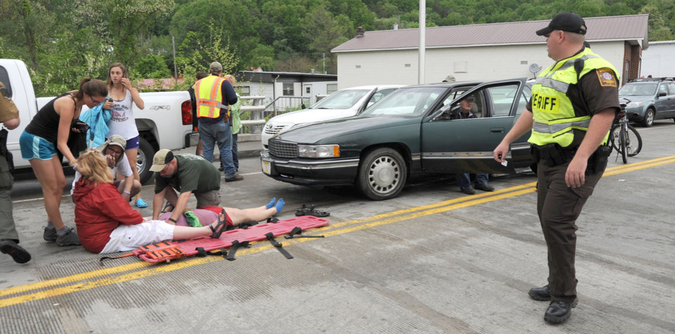 Photo - Emergency personnel respond to one of the people hit by a car, at right, during the beginning of the Hikers Parade at the Trail Days festival in Damascus, Va., Saturday, May 18, 2013. Witnesses said the car drove into a crowd at the parade and hurt several people, but the nature of their injuries wasn't immediately known. (AP Photo/Bristol Herald Courier, Earl Neikirk)