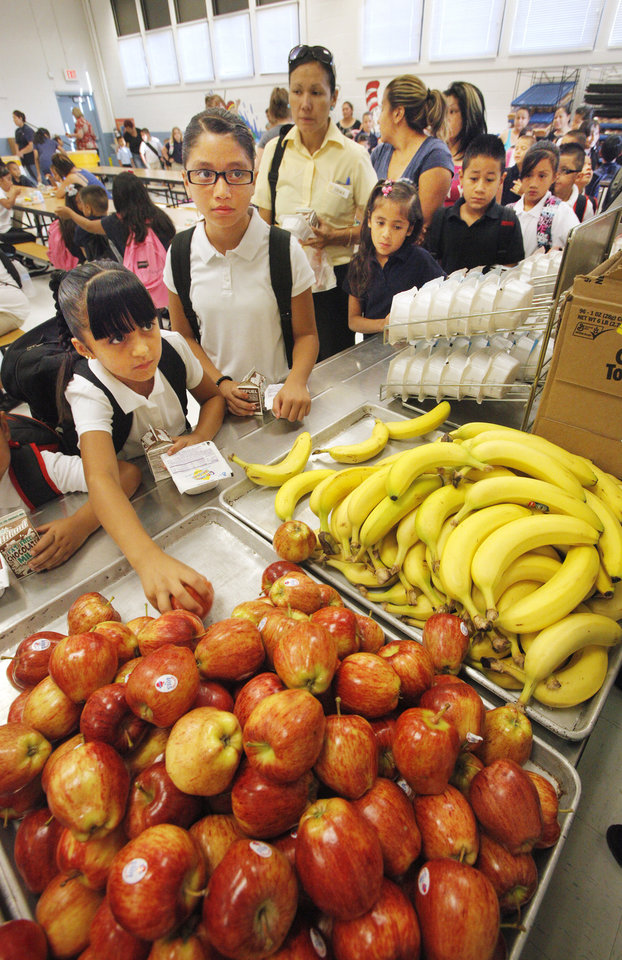 Photo - Students in the food line selecting breakfast fruit before classes start for the day at Adams Elementary in Oklahoma City Wednesday, Aug. 1, 2012. Wednesday was the first day of classes in the Oklahoma City Public School District.  Photo by Paul B. Southerland, The Oklahoman