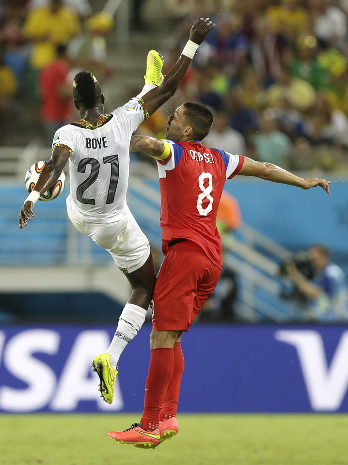 Photo - Ghana's John Boye, left, challenges United States' Clint Dempsey for the ball during the group G World Cup soccer match between Ghana and the United States at the Arena das Dunas in Natal, Brazil, Monday, June 16, 2014. (AP Photo/Ricardo Mazalan)