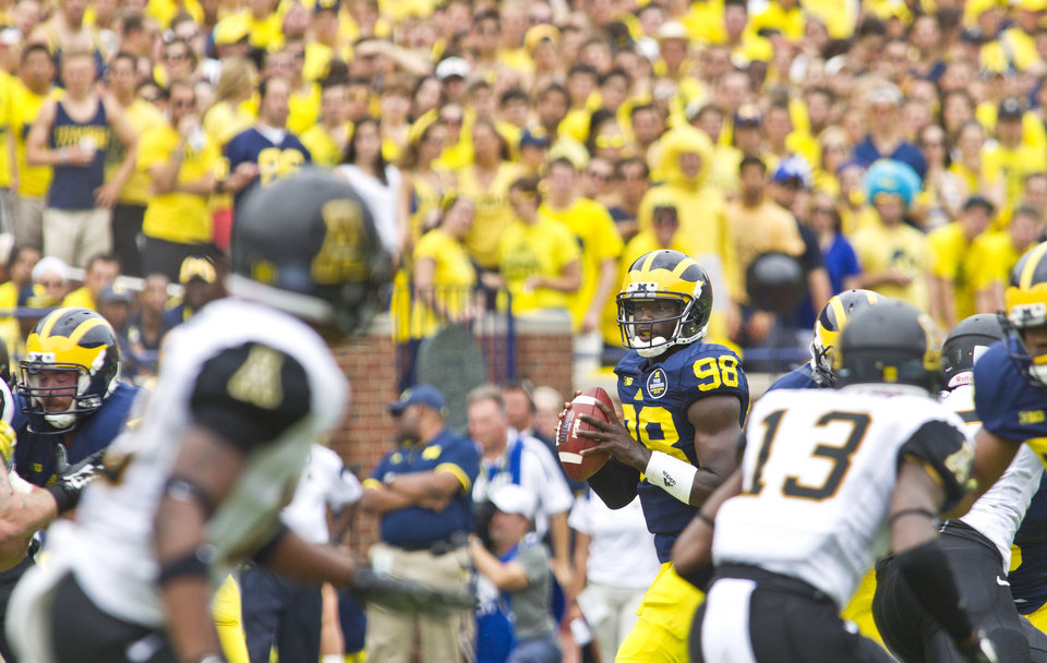 Photo - Michigan quarterback Devin Gardner (98) looks for an open receiver in the second quarter of an NCAA college football game against Appalachian State in Ann Arbor, Mich., Saturday, Aug. 30, 2014. (AP Photo/Tony Ding)