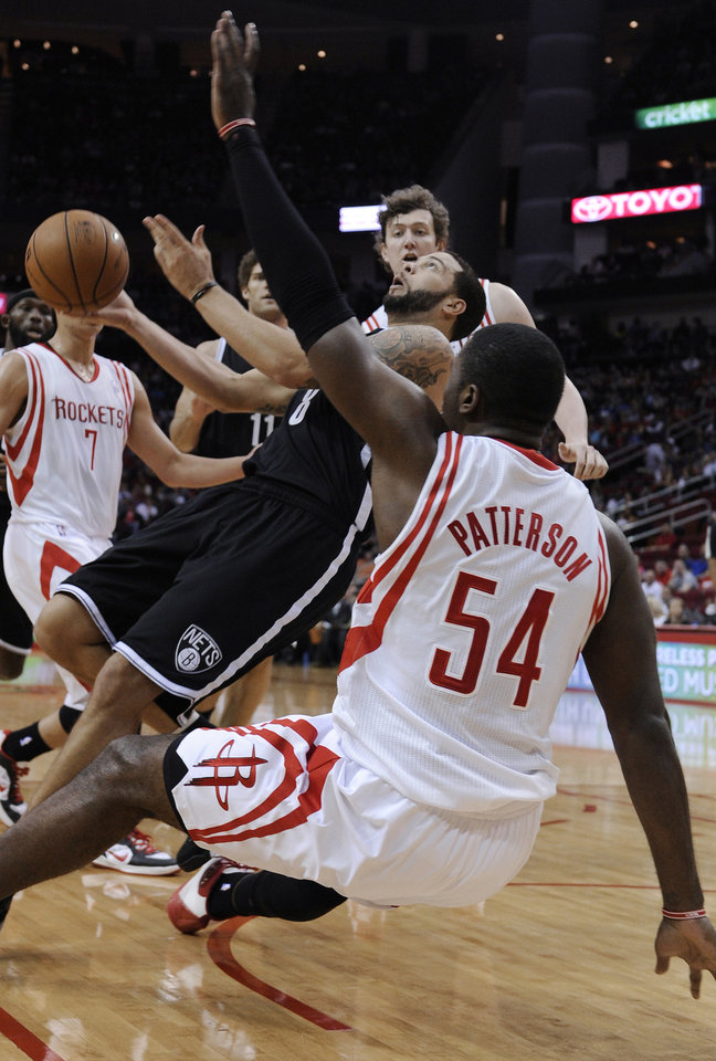 Photo - Brooklyn Nets' Deron Williams (8) tries to get off a shot as he falls over Houston Rockets' Patrick Patterson (54) in the first half of an NBA basketball game Saturday, Jan. 26, 2013, in Houston. (AP Photo/Pat Sullivan)