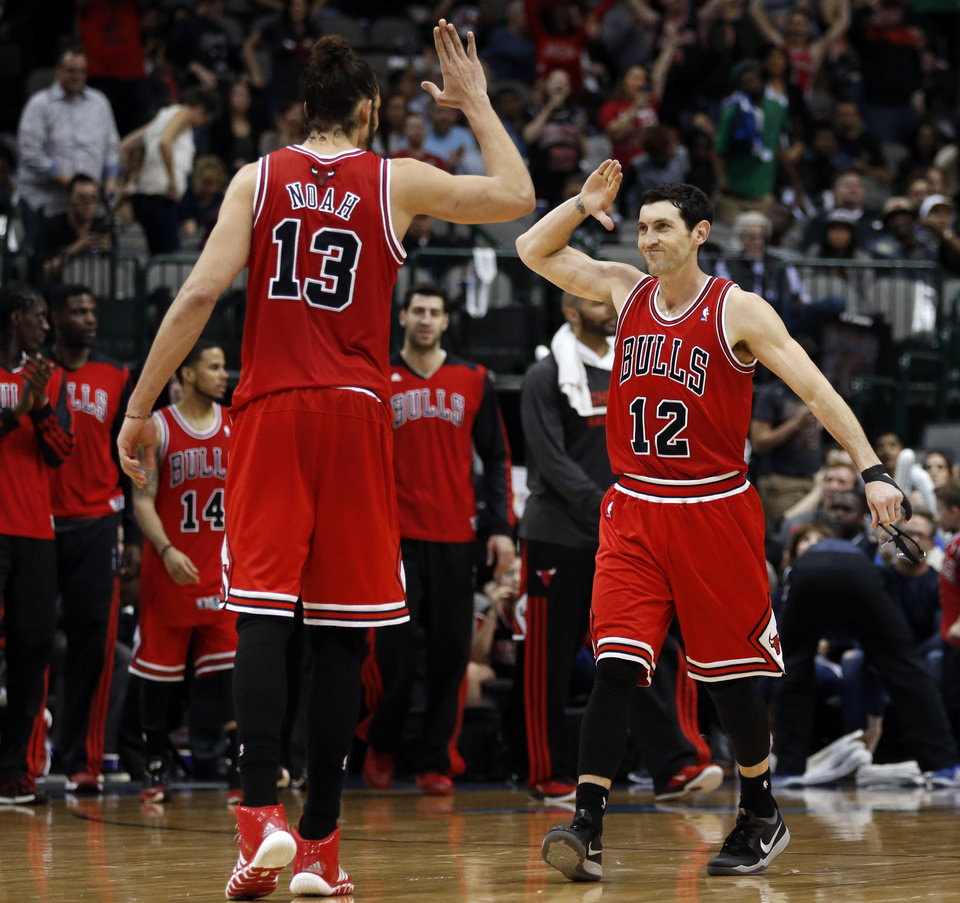 Photo - Chicago Bulls center Joakim Noah (13) and guard Kirk Hinrich (12) celebrate at the end of the team's 100-91 comeback win over the Dallas Mavericks in an NBA basketball game on Friday, Feb. 28, 2014, in Dallas. (AP Photo/John F. Rhodes)