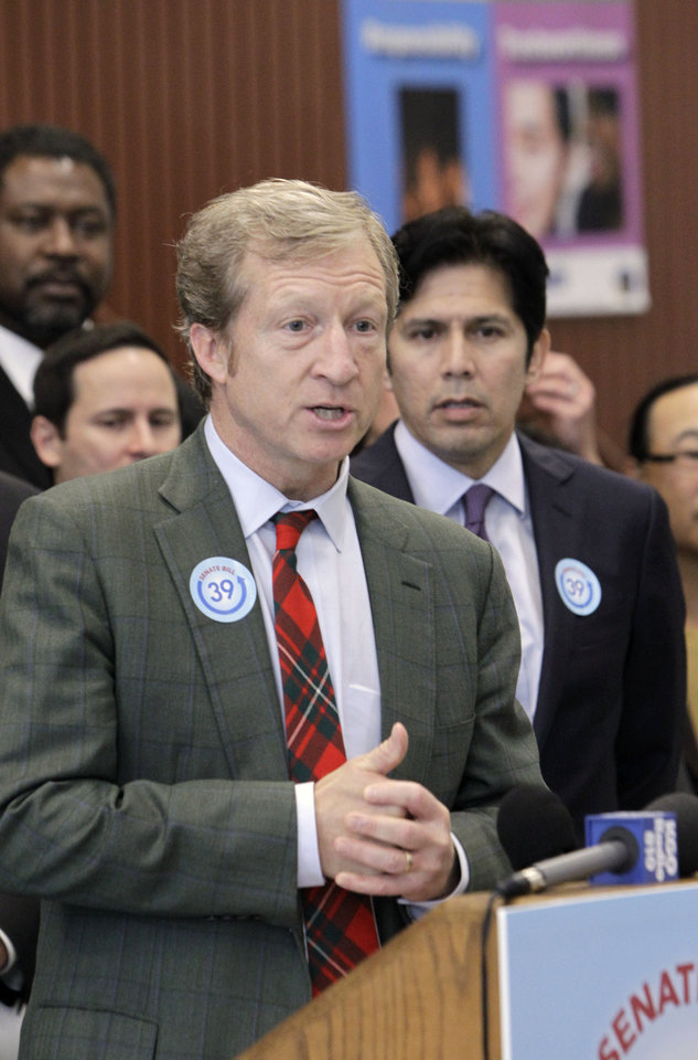 Photo - Billionaire Tom Steyer, the chief financier behind the Proposition 39 campaign, discusses a proposed bill to fund energy efficiency projects at schools in California's poorest communities, during a news conference at Mark Twin Elementary School in Sacramento, Calif., Tuesday, Dec. 4, 2012.  The bill, co-authored by state Sen. Kevin de Leon, D-Los Angles, right, and Senate President Pro Tem Darrell Steinberg, D-Sacramento, unseen,  would use money from last month's voter approved initiative, Proposition 39, that requires $500 million for five years be used for clean air project.(AP Photo/Rich Pedroncelli)