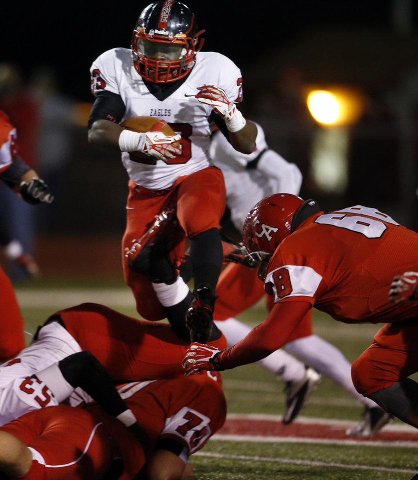 Photo - Del City's Anthony Mason leaps over tacklers in high school football action as the Carl Albert Titans play the Del City Eagles on Friday, Nov. 15, 2013 in Midwest City, Okla. Photo by Steve Sisney, The Oklahoman