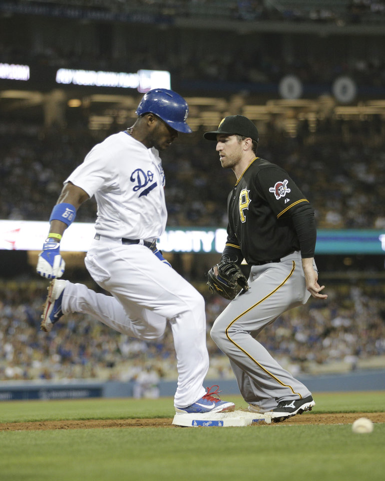 Photo - Los Angeles Dodgers' Yasiel Puig, left, takes first base as Pittsburgh Pirates first baseman Ike Davis misses the throw during the fourth inning of a baseball game Friday, May 30, 2014, in Los Angeles. (AP Photo/Jae C. Hong)