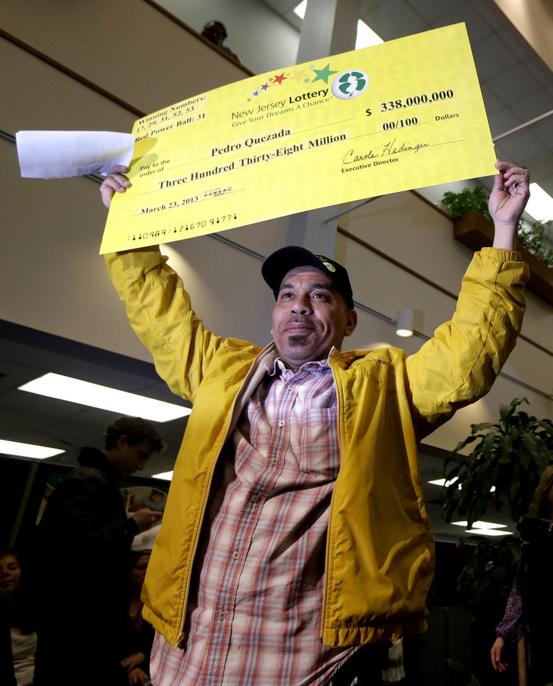 Photo - Pedro Quezada, the winner of the Powerball jackpot, holds up a promotional check during a news conference at the New Jersey Lottery headquarters, Tuesday, March 26, 2013, in Lawrenceville, N.J. Quezada , 44, won the $338 million jackpot with the winning ticket he purchased at Eagle Liquors store in Passaic, N.J. (AP Photo/Julio Cortez)