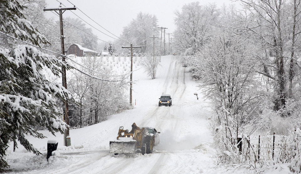 Photo - A tractor is used unsuccessfully to try to pull a stuck car up a snow slick hill on Mt. Tabor Rd., Sunday, Jan. 5, 2014, in Ellettsville, Ind. (AP Photo/Bloomington Herald-Times, Jeremy Hogan)