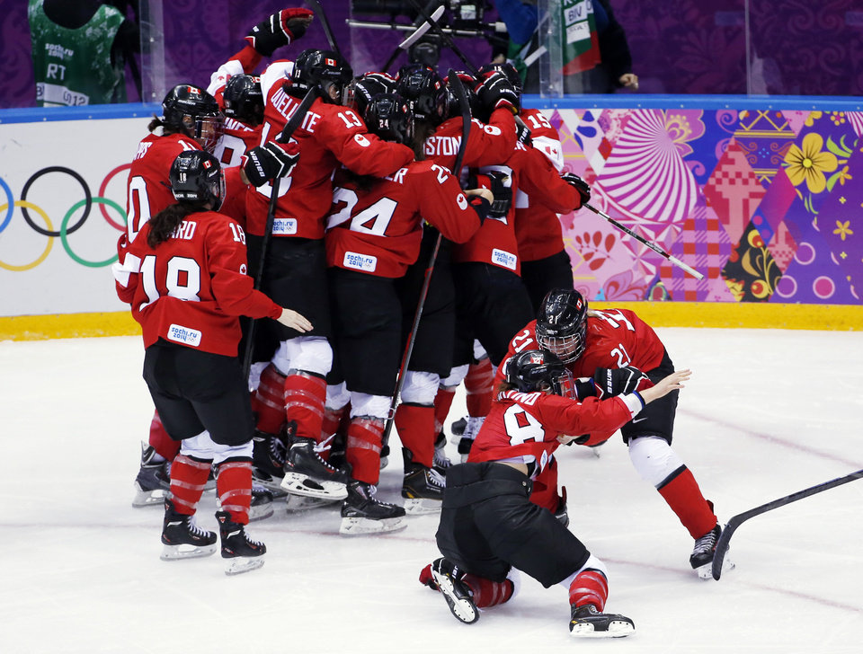 Photo - Canada celebrates after their 3-2 win in overtime against USA in the women's gold medal ice hockey game at the 2014 Winter Olympics, Thursday, Feb. 20, 2014, in Sochi, Russia. (AP Photo/Petr David Josek)