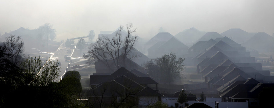 Smoke flows over the houses in the Oakwood East Royale neighborhood in Midwest City, Thursday, April 9, 2009. Photo by Bryan Terry, The Oklahoman