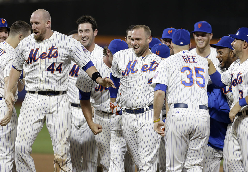Photo - New York Mets' Andrew Brown, center, celebrates his game winning single with his teammates during the 13th inning of the baseball game against the Arizona Diamondbacks at Citi Field, Tuesday, July 2, 2013, in New York. The Mets beat the Diamondbacks 5-4. (AP Photo/Seth Wenig)
