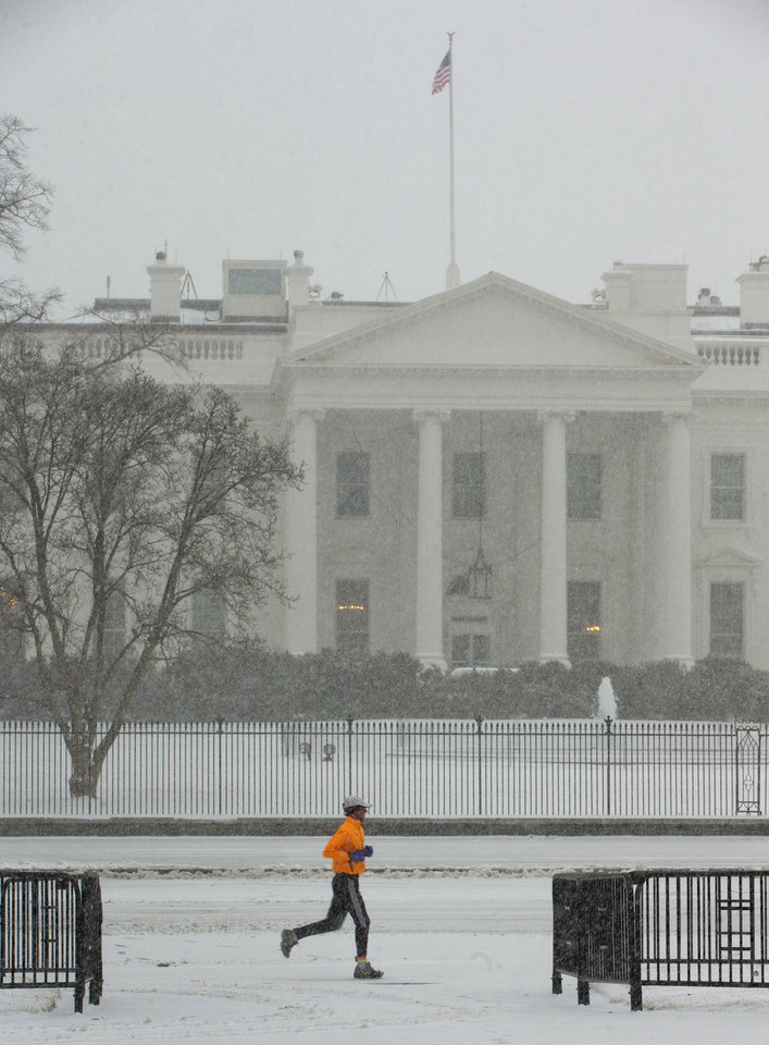 Photo - A jogger is seen in Lafayette Park in the snow front of the White House in Washington, Monday, March 3, 2014. The National Weather Service has issued a Winter Storm Warning for the greater Washington Metropolitan region, prompting area schools and the federal government to close for the wintry weather.  (AP Photo/Pablo Martinez Monsivais)
