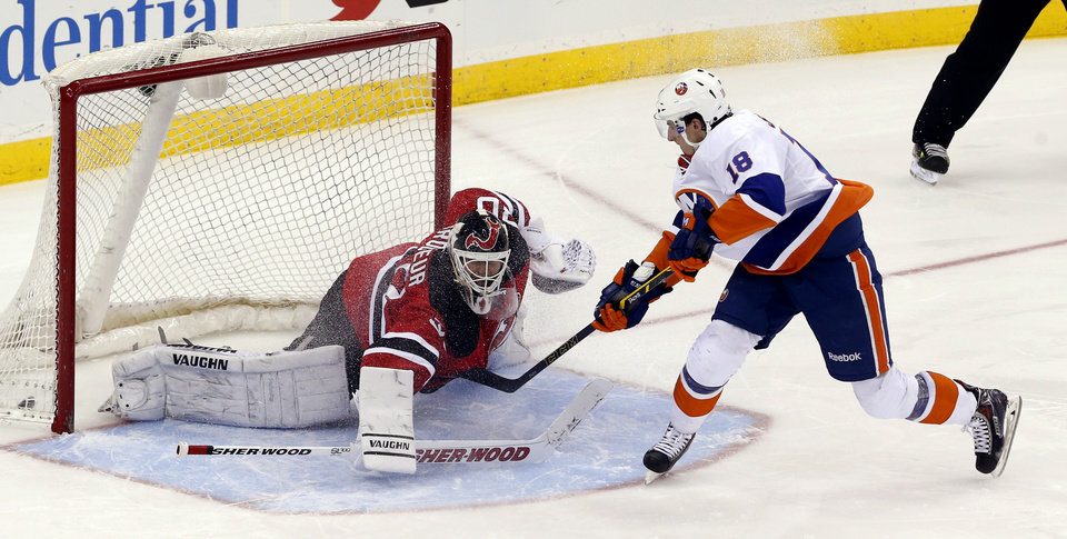 Photo - New York Islanders' Ryan Strome (18) scores a goal on New Jersey Devils goalie Martin Brodeur (30) to give the Islanders a 3-2 shootout victory in an NHL hockey game on Friday, April 11, 2014, in Newark, N.J. (AP Photo/Julio Cortez)