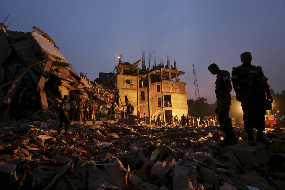 Photo - Bangladeshi soldiers stand in the rubble at the site of a building that collapsed Wednesday in Savar, near Dhaka, Bangladesh, Friday, April 26, 2013. By Friday, the death toll reached at least 270 people as rescuers continued to search for injured and missing, after a huge section of an eight-story building that housed several garment factories splintered into a pile of concrete. (AP Photo/Kevin Frayer)