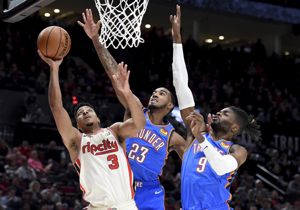 Photo - Portland Trail Blazers guard CJ McCollum, left, drives to the basket as Oklahoma City Thunder guard Terrance Ferguson, center, and center Nerlens Noel, right, defend during the second half of an NBA basketball game in Portland, Ore., Wednesday, Nov. 27, 2019. The Blazers won 136-119. (AP Photo/Steve Dykes)