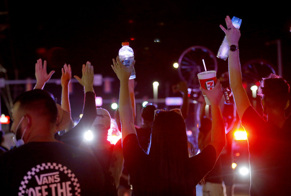 Photo - Protesters hold their hands on Pennsylvania Avenue and NW23rd Street during a protest near the intersection in Oklahoma City, Saturday, May 30, 2020. The protest was in response to the death of George Floyd. [Sarah Phipps/The Oklahoman]