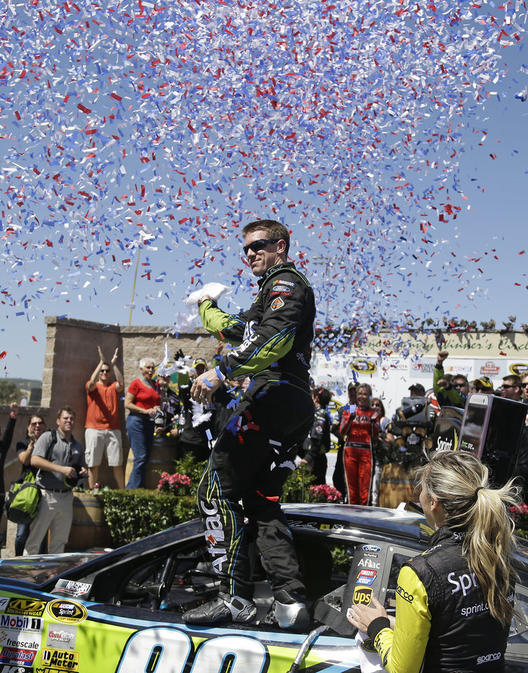 Photo - Carl Edwards stands atop his car after winning the NASCAR Sprint Cup Series auto race on Sunday, June 22, 2014, in Sonoma, Calif. Gordon finished in second place. (AP Photo/Eric Risberg)