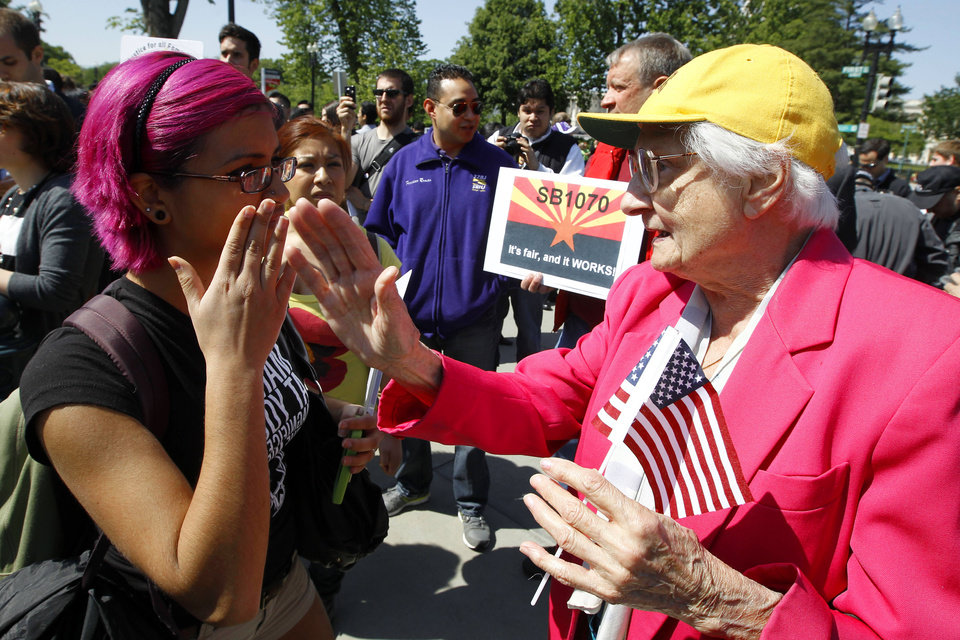 Supporters for and against Arizona\'s immigration law argue outside the Supreme Court in Washington, Wednesday, April 25, 2012, where the court held a heating on Arizona\'s