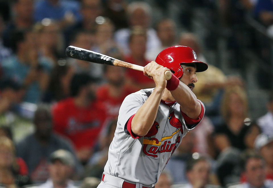 Photo - St. Louis Cardinals third baseman Matt Carpenter (13) follows through with a two-run double in the fifth inning of a baseball game against the Atlanta Braves Monday, May 5, 2014 in Atlanta.  (AP Photo/John Bazemore)
