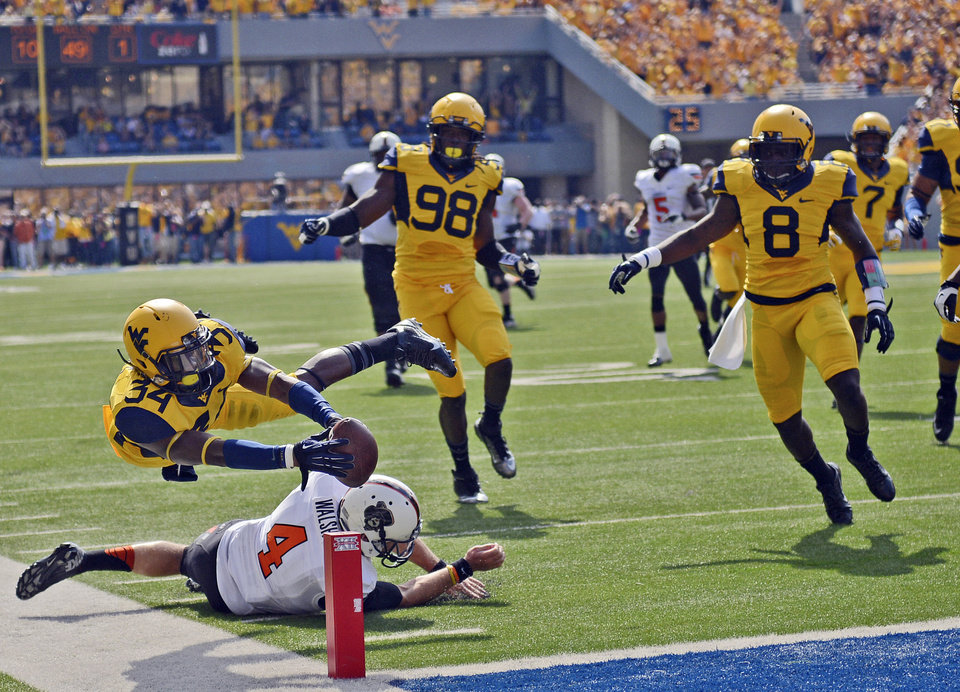 Photo - West Virginia' Ishmael Banks (34) reaches over the goal line for touchdown after returning an interction 58-yard for the score during the first quarter of an NCAA college football game Oklahoma State in Morgantown, W.Va., on Saturday, Sept. 28, 2013. (AP Photo/Tyler Evert) ORG XMIT: WVTE101