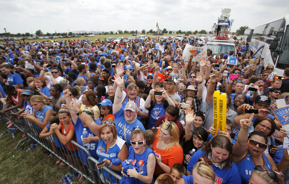 Photo - Fans cheer as the Thunder leave a welcome home rally for the Oklahoma City Thunder in a field at Will Rogers World Airport after the team's loss to the Miami Heat in the NBA Finals, Friday, June 22, 2012. Photo by Nate Billings, The Oklahoman