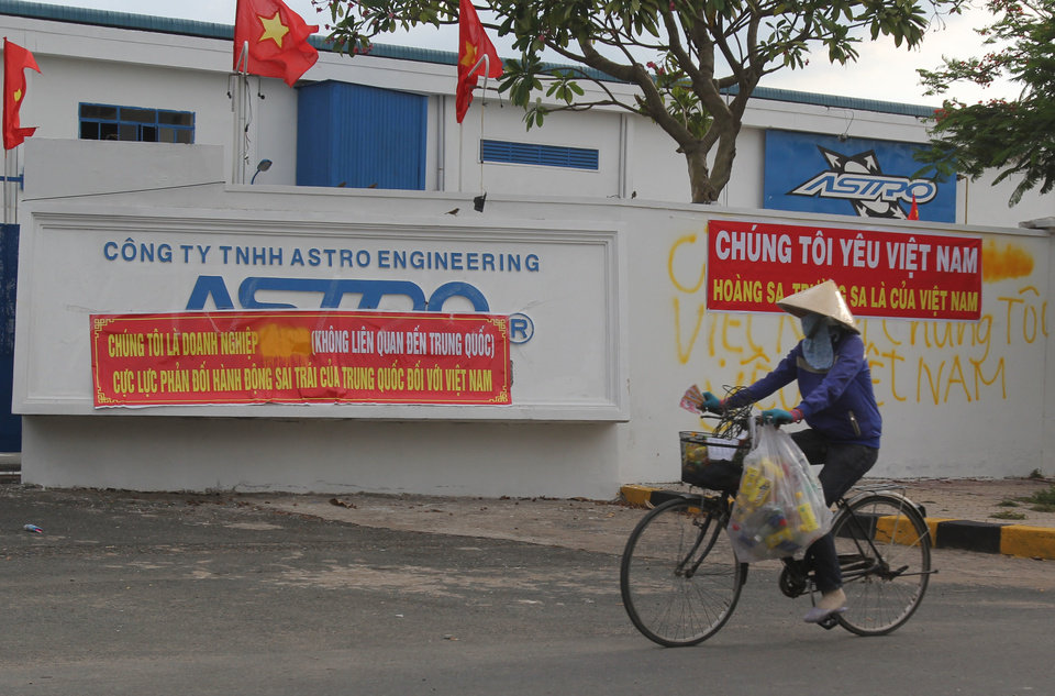 Photo - A woman cycles past a closed factory in an industrial park in Binh Duong province, Vietnam Saturday, May 17, 2014, five days after mobs attacked foreign owned factories following anti-China protests. Vietnam's prime minister ordered an end Saturday to all