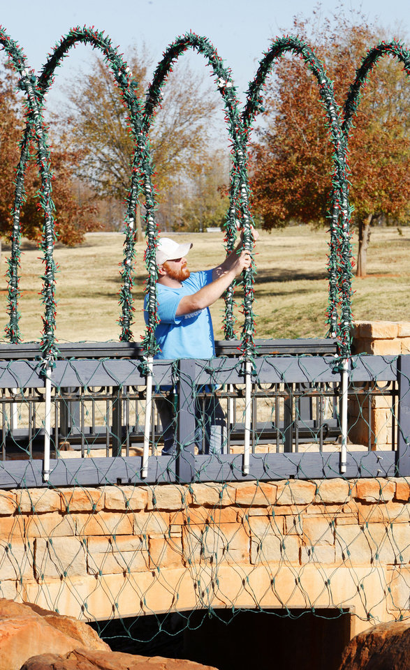 Photo - Yukon city worker Nick Rice strings Christmas lights on a bridge at Chisholm Trail Park.