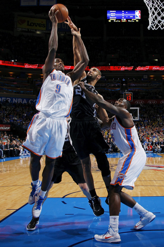 Photo - Oklahoma City's Serge Ibaka (9) shoots as San Antonio's Tim Duncan (21) defends next to Oklahoma City's Kendrick Perkins (5) during an NBA basketball game between the Oklahoma City Thunder and the San Antonio Spurs in Oklahoma City Monday, Dec. 17, 2012. Oklahoma City won, 107-93. Photo by Nate Billings, The Oklahoman