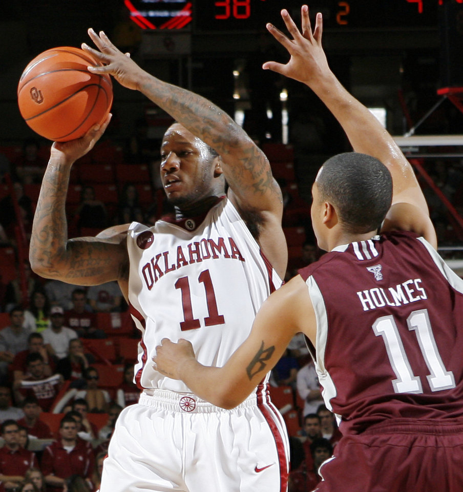 Photo - OU's Tommy Mason-Griffin passes the ball away from B.J. Holmes of Texas A&M in the second half during the men's college basketball game between the Oklahoma Sooners and Texas A&M Aggies at Lloyd Noble Center in Norman, Okla., Saturday, March 6, 2010. Texas A&M won, 69-54. Photo by Nate Billings, The Oklahoman