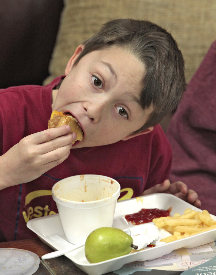 Photo -      Fifth-grader Chase Crutchfield eats a sandwich during Reading Club at Stanley Hupfeld Academy on Thursday. Photo by David McDaniel, The Oklahoman   David McDaniel -  The Oklahoman