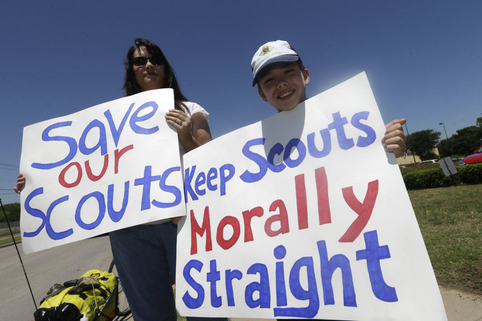 Photo - Terri Hall, left, of San Antonio, Texas, stands with her son Nathaniel Hall, 8, as they hold signs near where the Boy Scouts of America are holding their annual meeting Wednesday, May 22, 2013, in Grapevine, Texas. Delegates to the meeting are expected to address a proposal to allow gay scouts into the organization. (AP Photo/LM Otero)