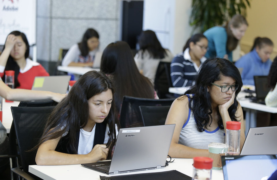 Photo - In this photo taken Wednesday, June 18, 2014, Bryanna Gilges, 15, left, and Yvonne Gonzalez, 17, right, work at completing an exercise during a Girls Who Code class at Adobe Systems in San Jose, Calif. Girls Who Code, a national non-profit organization that aims to inspire, educate and equip young women for futures in the computing-related fields, kicked off its summer program in partnership with the world's leading tech companies. The Summer Immersion Program will reach 380 high school girls across 19 classes in New York, Boston, Miami, Seattle and the Bay Area. Fewer than one percent of high school girls think of computer science as part of their future, even though it's one of the fastest growing fields in the U.S. today with a projected 4.2 million jobs by 2020, according to the Bureau of Labor Statistics.(AP Photo/Eric Risberg)