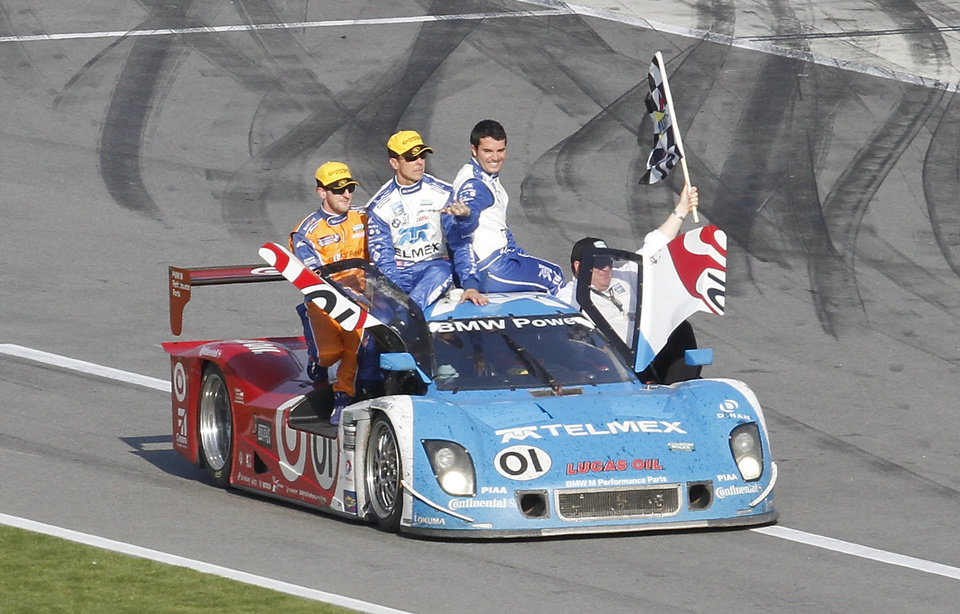 Photo - Juan Pablo Montoya, of Colombia, drives the Ganassi Racing BMW Riley down pit road with teammates on the car, from left, Charlie Kimball, Scott Pruett, Memo Rojas, of Mexico, and team owner Chip Ganassi waving the checker flag after winning the Grand-Am Series Rolex 24 hour auto race at Daytona International Speedway, Sunday, Jan. 27, 2013, in Daytona Beach, Fla. (AP Photo/David Graham)