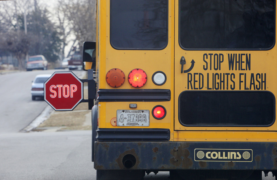 Photo -      An Oklahoma City Public School bus with the stop sign out and flashing picks up a student at Park Avenue and Blackwelder Avenue in Oklahoma City on March 7. Photo by Paul B. Southerland, The Oklahoman   PAUL B. SOUTHERLAND - PAUL B. SOUTHERLAND