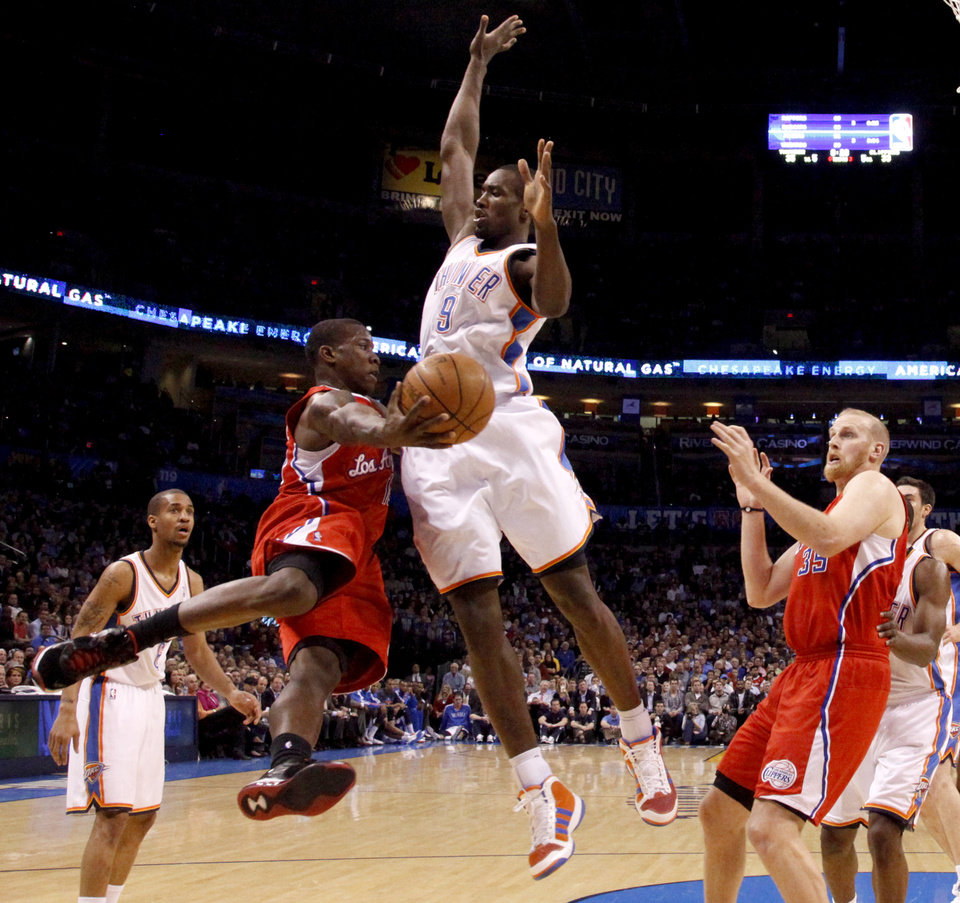 Photo - Oklahoma City's Serge Ibaka (9) defends Los Angeles' Eric Bledsoe (12) during the NBA basketball game between the Oklahoma City Thunder and the Los Angeles Clippers at the Oklahoma CIty Arena, Tuesday, Feb. 22, 2011.  Photo by Bryan Terry, The Oklahoman