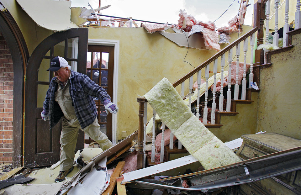 Photo - Bob Haslam navigates his way down stairs as he helps remove items from his daughter's home that was heavily damaged in the Oak Tree addition on Wednesday, Feb. 11, 2009, after a tornado hit the area on Tuesday in Edmond, Okla.  PHOTO BY CHRIS LANDSBERGER, THE OKLAHOMAN