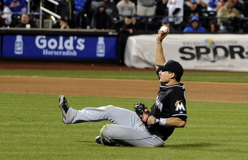 Photo - Miami Marlins second baseman Derek Dietrich slides to catch a fly ball hit by New York Mets' Omar Quintanilla in the seventh inning of a baseball game at Citi Field on Friday, April 25, 2014, in New York. (AP Photo/Kathy Kmonicek)