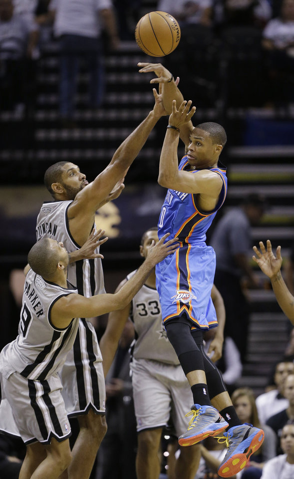 Photo - Oklahoma Thunder's Russell Westbrook, right, passes over San Antonio Spurs' Tim Duncan, center and Tony Parker, left, of France, during the second quarter of an NBA basketball game, Thursday, Nov. 1, 2012, in San Antonio. (AP Photo/Eric Gay) ORG XMIT: TXEG105