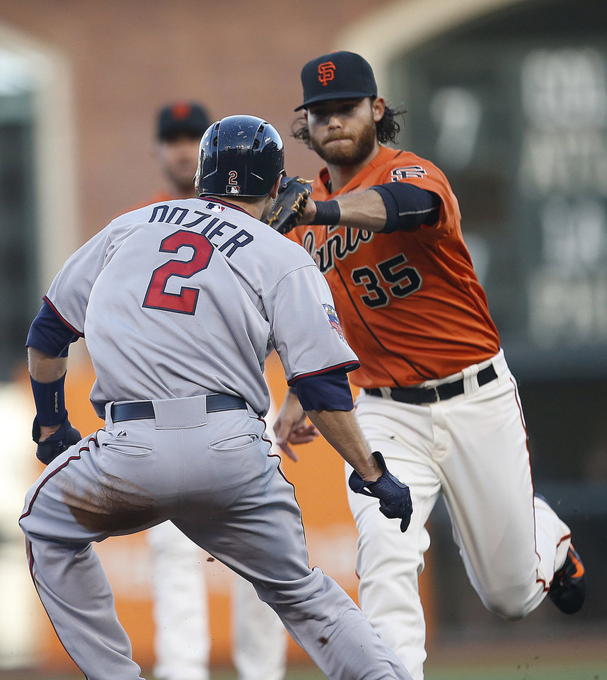 Photo - San Francisco Giants shortstop Brandon Crawford (35) tags out  Minnesota Twins' Brian Dozier (2) as he tried to steal third base in the first inning of a baseball game Friday, May 23, 2014, in San Francisco. (AP Photo/Tony Avelar)