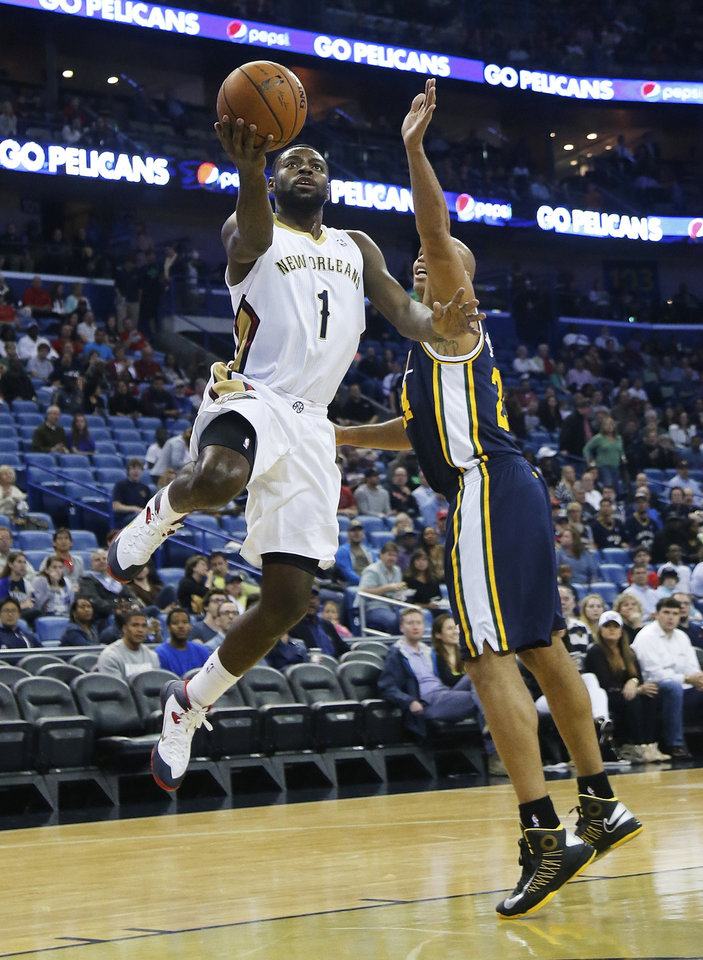 New Orleans Pelicans forward Tyreke Evans (1) drives to the basket for two of his 22-points as Utah Jazz guard Gordon Hayward (20) defends in the first half of an NBA basketball game in New Orleans, Friday, March 28, 2014. The Pelicans defeated the Jazz 102-95. (AP Photo/Bill Haber)