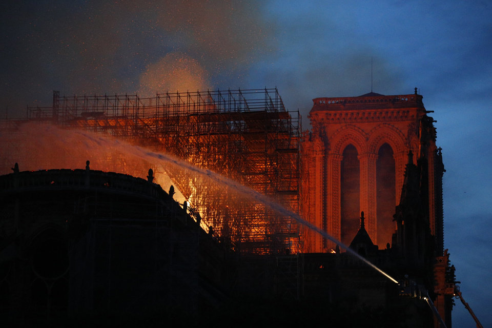 Photo - Firefighters use hoses as Notre Dame cathedral burns in Paris, Monday, April 15, 2019. A catastrophic fire engulfed the upper reaches of Paris' soaring Notre Dame Cathedral as it was undergoing renovations Monday, threatening one of the greatest architectural treasures of the Western world as tourists and Parisians looked on aghast from the streets below. (AP Photo/Francois Mori)