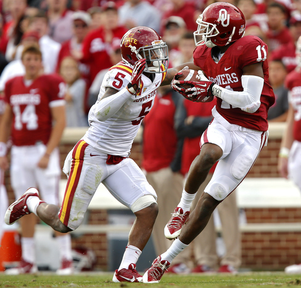 Oklahoma's Lacoltan Bester (11) makes a catch from Kendal Thompson (1) in front of Iowa State's Jacques Washington (5) during the college football game between the University of Oklahoma Sooners (OU) and the Iowa State University Cyclones (ISU) at Gaylord Family-Oklahoma Memorial Stadium in Norman, Okla. on Saturday, Nov. 16, 2013. Photo by Chris Landsberger, The Oklahoman