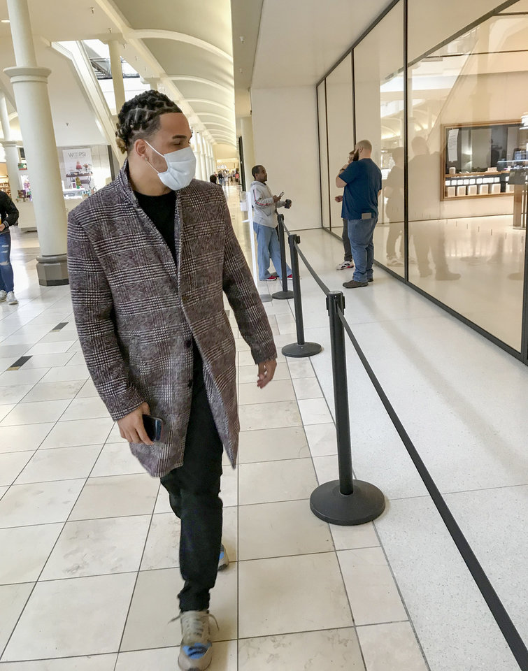 Photo - Kevin Garcia of Oklahoma City wears a mask as he walks past the Apple Store in Penn Square Mall in Oklahoma City, Friday, March 13, 2020. Garcia had come to the mall to go to the Apple Store, which is closed along with Apple's other retail stores until at least March 27 because of the coronavirus pandemic. Garcia said he started wearing the mask today specifically for his trip to the mall. [Nate Billings/The Oklahoman]