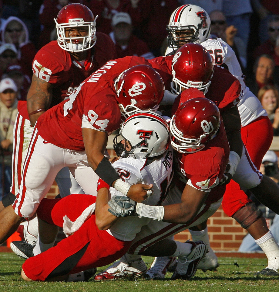 Photo - Jeremy Beal (44), Pryce Macone (94) and Jamarkus McFarland (behind) bring down quarterback Taylor Potts (12) during the first half of the college football game between the University of Oklahoma Sooners (OU) and the Texas Tech Red Raiders (TTU) at the Gaylord Family Memorial Stadium on Saturday, Nov. 13, 2010, in Norman, Okla.  Photo by Steve Sisney, The Oklahoman
