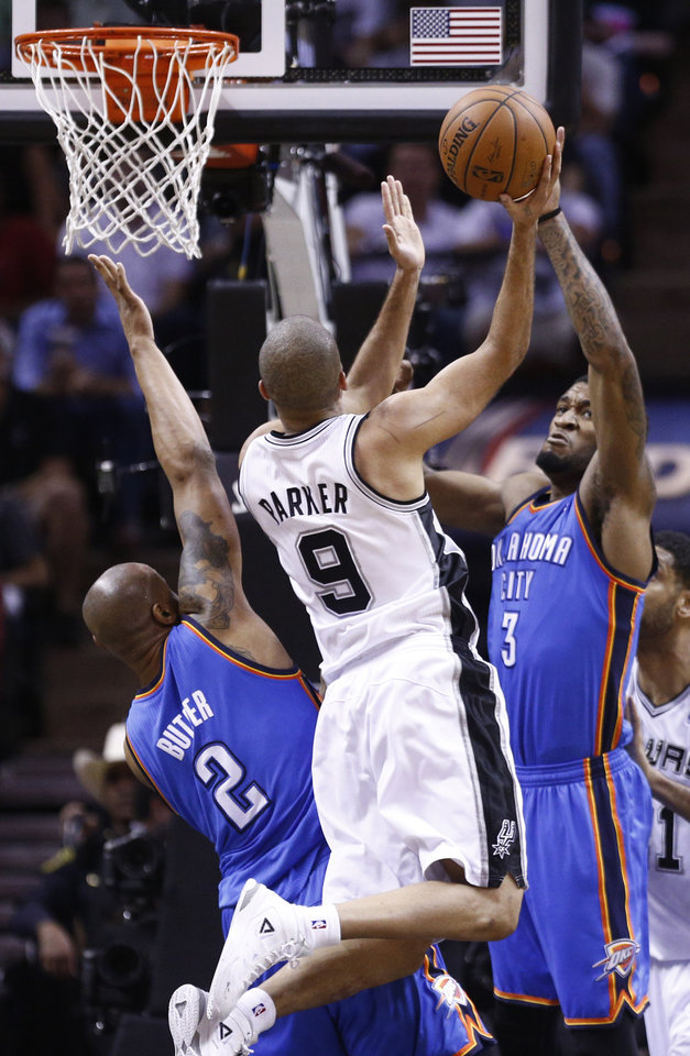 Photo - San Antonio's Tony Parker (9) shoots a basket at Oklahoma City's Caron Butler (2) and Perry Jones (3) defend during Game 2 of the Western Conference Finals in the NBA playoffs between the Oklahoma City Thunder and the San Antonio Spurs at the AT&T Center in San Antonio, Wednesday, May 21, 2014. Photo by Sarah Phipps