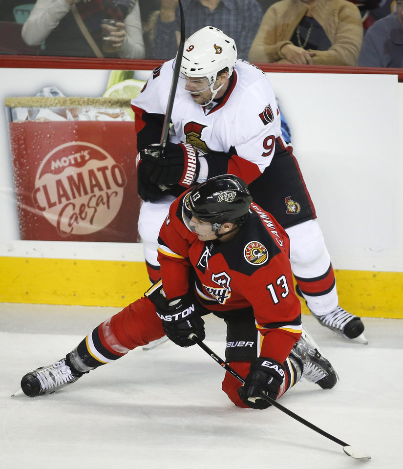 Photo - Ottawa Senators' Milan Michalek, top, from the Czech Republic, knocks Calgary Flames' Mike Cammalleri to the ice during the second period of an NHL hockey game Wednesday, March 5, 2014, in Calgary, Alberta. (AP Photo/The Canadian Press, Jeff McIntosh)
